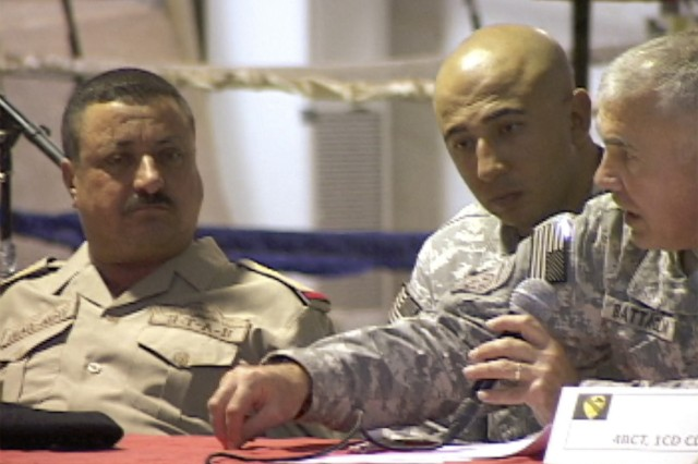 Colonel Philip Battaglia, the 4th BCT, 1st Cav. Div. commander, stresses a point to Maj. Gen. Habib, the 10th IA Div. commanding general, at the end of a logistics conference held in Tallil Oct. 11.