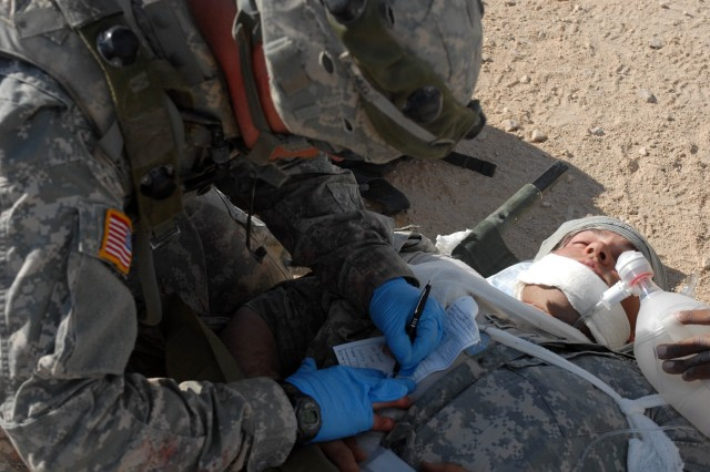 A medic with Headquarters and Headquarters Battery, 1st Battalion, 82nd Field Artillery Regiment, 1st Brigade Combat Team, 1st Cavalry Division, fills out a field medical card for a simulated patient after the FOB was hit by simulated mortar fire Oct. 16.  The soldiers practiced the proper procedures during a mass casualty training exercises.
