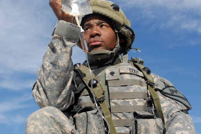 Atlanta, Ga. Native, Spc. Edward Cody, armor, Headquarters and Headquarters Battery, 1st Battalion, 82nd Field Artillery Regiment, 1st Brigade Combat Team, 1st Cavalry Division, holds an I.V. and manually pumps oxygen into the lungs of a simulated casualty at the National training center, on Ft. Irwin Calif. Oct. 16.