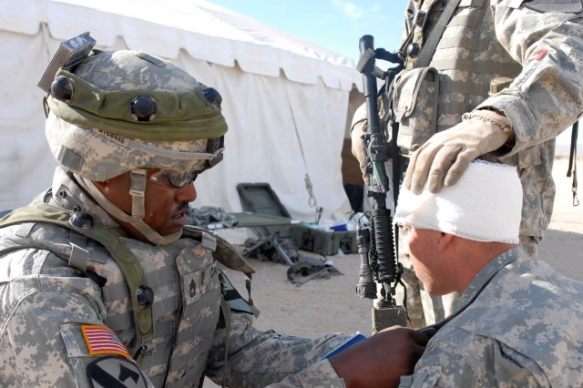 Philadelphia, Pa. native, Sgt 1st Class Reginold Carter, a platoon sergeant with Headquarters and Headquarters Battery, 1st Battalion, 82nd Field Artillery Regiment, 1st Brigade Combat Team, 1st Cavalry Division, tapes a field medical card to the chest of a simulated casualty, Oct. 16. The card is used so that medical personnel can quickly identify injury, and care given before the patient reaches their location.