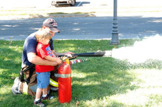 C.J. Cox, age 2, learns how to use a fire extinguisher during the Carlisle Barracks Kids Fire Academy on Oct. 13. Josh Yale, Carlisle Barracks firefighter, taught kids how to stay safe and be ready in the event of a fire.