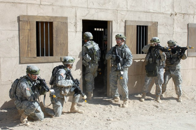 """Soldiers from Delta Company 2nd """"Lancers"""" Battalion, 5th Cavalry Regiment, 1st Brigade Combat Team, 1st Cavalry Division pull security at the entrance of the building they used to secure their high value """"individual"""" Oct. 13 at the National Training Center, Calif."""