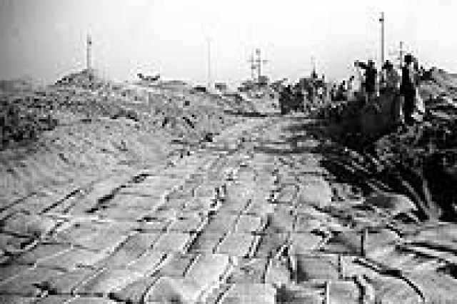"Photo #: NH 97056  Road paved with sand bags on ""Green"" Beach during the landing of the Seventh Infantry Division at Iwon, North Korea, circa late October 1950. Note Korean civilians filling sand bags at right, and LSTs in the background.  Official U.S. Navy Photograph, from the collections of the Naval Historical Center."