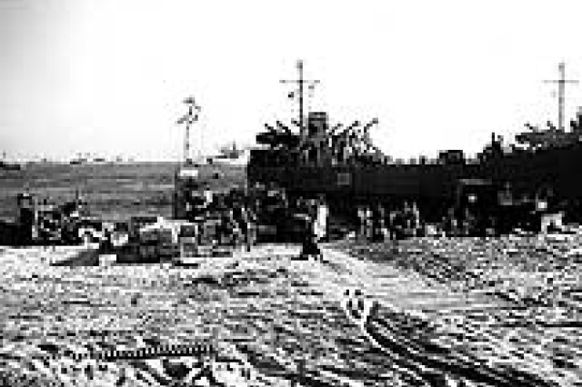"Photo #: NH 97055  A U.S. Navy LCT unloads trucks and other vehicles, as the Seventh Infantry Division is landed at Iwon, North Korea, circa late October 1950. Two bulldozers are among the vehicles already on the beach. LST at right bears the side number ""QO-74"". Note merchant-type shipping anchored offshore.  Official U.S. Navy Photograph, from the collections of the Naval Historical Center."