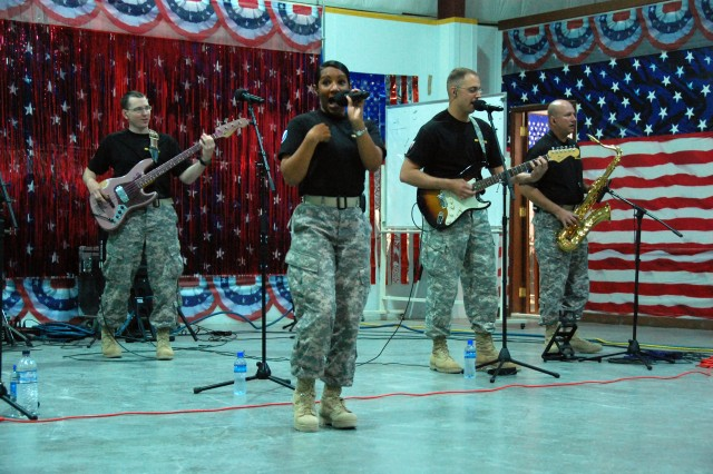 "Sgt. Ericka Escalante belts out the vocals to  ""Material Girl"" during a performance for members of the 401st Army Field Support Brigade, Oct. 26, 2008, at Camp Arifjan Kuwait.  Escalante and (L-R) Spc. Matt Smith, Sgt. 1st Class Stephen Spohn and Staff Sgt. Jeff Endly, along with other members of the U.S. Army Materiel Command's  rock band ""Raw Materiel"" are in Southwest Asia for a series of performances for Soldiers, DoD civilians and defense contractors."