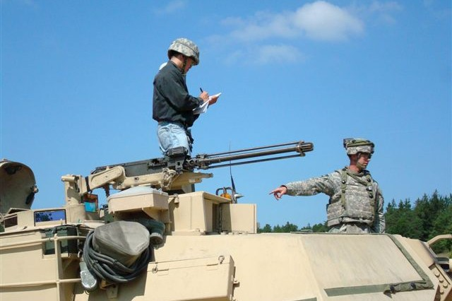 Picatinny engineer, Wei-Jen Su receives feedback from the crew of an M1 Abrams tank.
