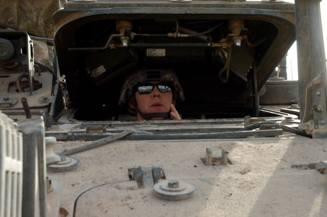 Spc. Tiffany Knotts peers out from the driverAca,!a,,cs hatch while performing her weekly Preventative Maintenance Checks and Services on her Stryker vehicle Oct. 13 at Camp Taji, northwest of Baghdad.