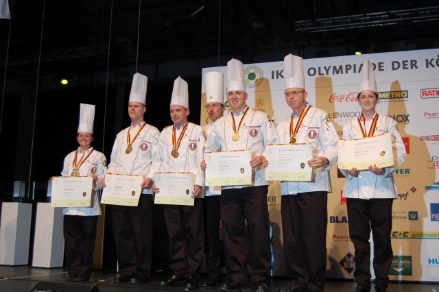 (Left to Right) Representing the U.S. Army Culinary Arts Team, Spc. Valine Vukich, Staff Sgt. Joshua Spiess, Senior Chief Petty Officer Justin Reed, German Chefs Association President Ctefan Wohlfeil, Staff Sgt. Steven Broome, Sgt. Matthew Flemister and Spc. Michelle Carville, receive a Gold Medal on the Olympic Stage Oct. 23 for their performance in the Hot Food Competition. Photo by Sarah Trier, Fort Lee Public Affairs