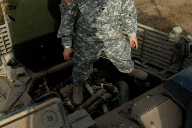 Spc. Tiffany Knotts stands on top of the engine block while performing her weekly Preventative Maintenance Check and Services on her Stryker vehicle Oct. 13 at Camp Taji, northwest of Baghdad. ,