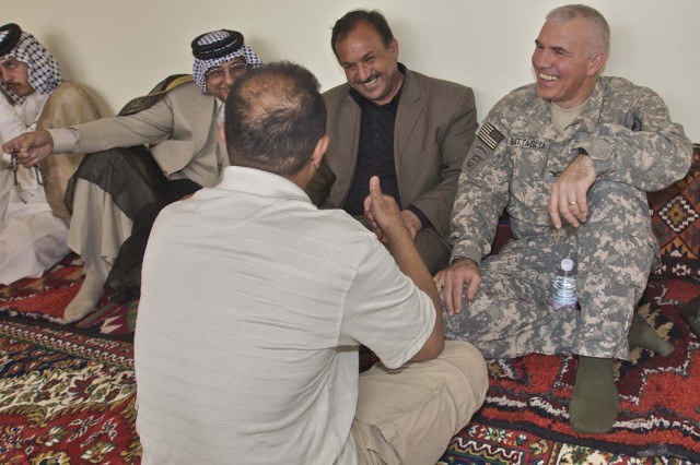 Col. Philip Battaglia, the commander of the 4th Brigade Combat Team, 1st Cavalry Division, speaks with a business leader from Nasiriyah with the help of his interpreter near the Ziggurat Oct. 23. The Catholic archbishop for Iraq and Jordan visited the Ziggurat and the Long Knife Brigade in Tallil, Iraq,