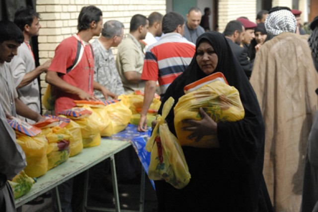 An Iraqi woman from Majarr al-Kabir, Iraq, receives food from the non-government food drop Oct. 25. The food was provided by the al-Yaq Dha al-Thaka Pia Foundation and Maysan PRT.