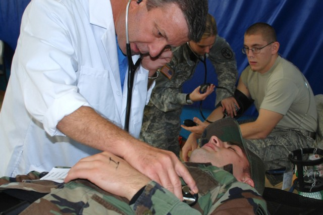 Dr. Ray Germano, a physician for the U.S. Army Garrison Livorno Health Clinic, examines a role player during an All Hazards force protection exercise Oct. 22 in Italy.
