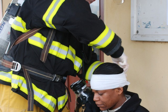 """Italian firefighter Luciano Lazzari bandages a """"wounded victim"""" from a train derailment scenario that was part of an All Hazards exercise at Camp Darby, Italy, Oct.22."""