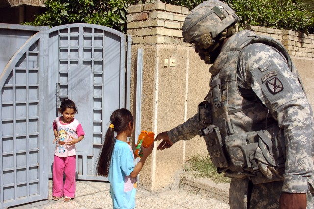 Sgt. 1st Class Calvin Cameron, a native of College Park, Ga., who serves in Multinational Division Baghdad as a fires support noncommissioned officer with the 10th Mountain Division's Brigade Support Troop Battalion, 4th Brigade Combat Team, meets with two students while conducting a humanitarian aid mission to assess the needs of a school in Beladiat, Iraq, Oct 9, 2008.