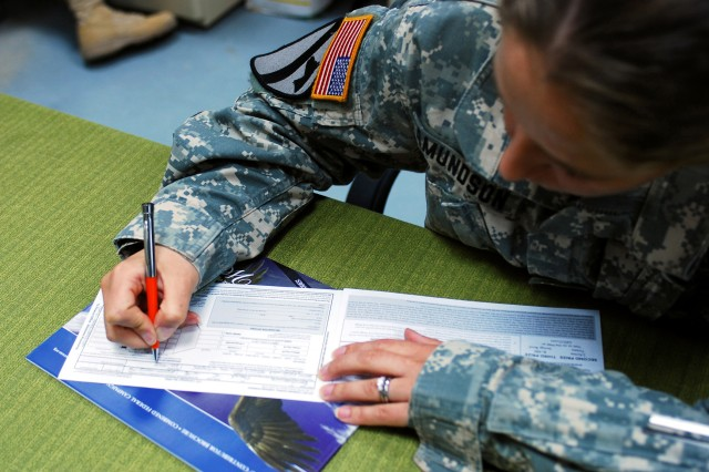 A Soldier fills out pledge forms for the Combined Federal Campaign-Overseas program. Program officials say donors in Europe can still contribute to the program in person or online through Dec. 3.