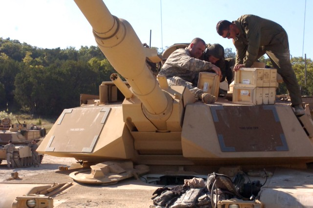 Soldiers from the 1st Battalion, 5th Regiment, 2nd Brigade Combat Team, 1st Cavalry Division load ammunition on to their tank before it returns to the range on Oct. 22 at Sugarloaf Multi-Use Range on Fort Hood. The Soldiers are training on all weapon systems on their tank at the range.