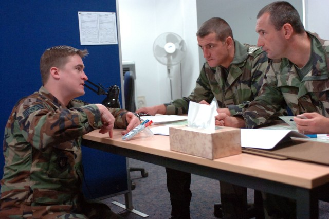 Air Force Staff Sgt. Brett Sternal (left) briefs a pair of French soldiers as they prepare to make a simulated call for Close Air Support at the Joint Multinational Readiness Center in Hohenfels. Allied forces are training for an upcoming deployment to Afghanistan.