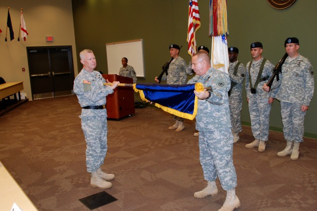 """Maj. Gen. Charles E. Gorton, commander of the 81st Regional Support Command, lowers the cased colors as Command Sgt. Maj. Luis Blanco unveils the """"Wildcat"""" colors of the historic 81st Division during the uncasing ceremony held Sept. 26 at Fort"""