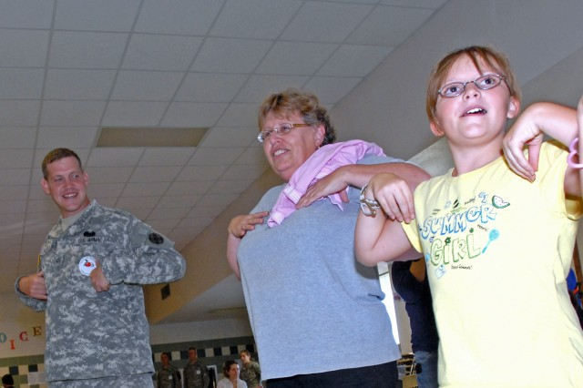 "Private 1st Class Neal Romain, a 565th Quartermaster supply specialist, does the ""Chicken Dance"" with teachers and students of Clarke Elementary while volunteering at the school's sock hop dance here, Oct. 24."