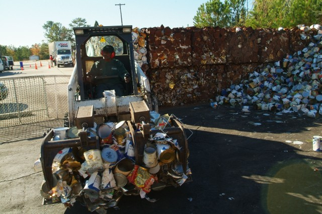 A worker moves and stacks steel cans collected for recycling at the Fort Jackson, S.C. recycling center.