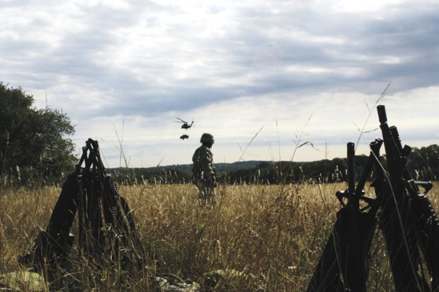 Staff Sgt. Andre Barnes, platoon sergeant with the 418th Medical Logistics Company, watches a Black Hawk helicopter transport a humvee during a field training exercise Oct. 23 at Camp Bullis. More than 200 Soldiers from the 61st Multifunctional Medical Battalion participated in the medical logistics operation.