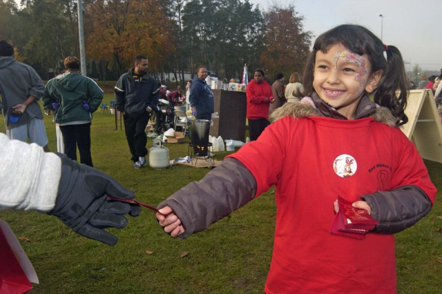 Yvette Mendoza, 6, a Ramstein Elementary School first grader, hands out red ribbons Oct. 25 at the U.S. Army Garrison Kaiserslautern's Red Ribbon Relay held in Germany.  More than 630 Soldiers, Airmen, civilians and their family members ran laps - more than double the number of people who participated last year.