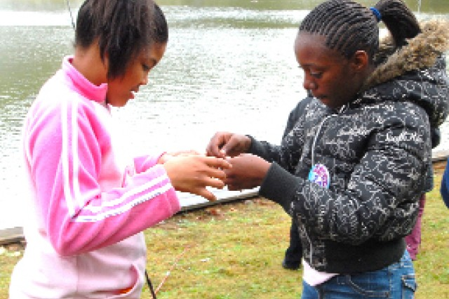 Adranique Phillips, 11, gets help baiting a hook from Devantae Hunns, 11,  a College Park resident. Adranique and her brother Aaron live with their mother, Latonia Phillips, in East Point.