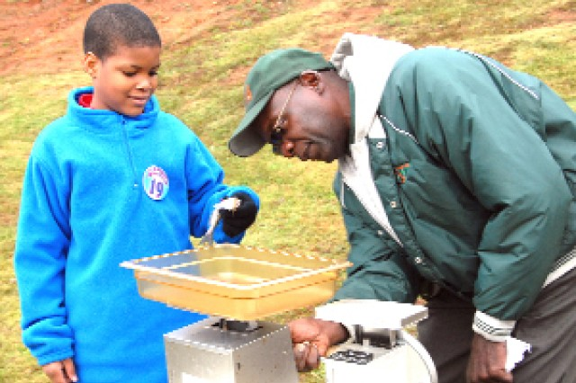 William D. Roberson Jr., of Unified Bass Master of Atlanta Bass Club, adjusts the scales to weigh a catfish caught by Aaron Phillips, 10, from East Point.