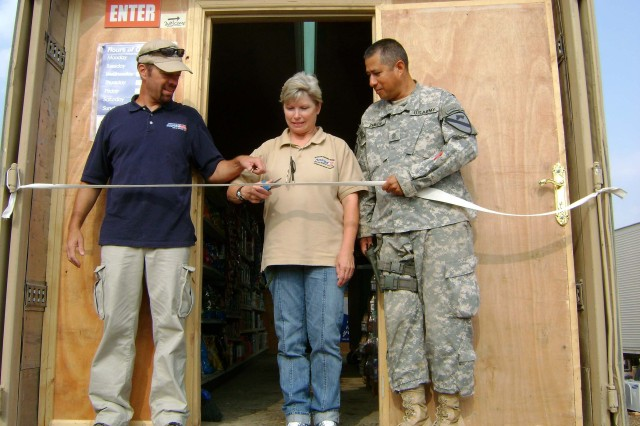 Joel Kelso, Cheri New and Command Sgt. Maj. George Zamudio, command sergeant major of 2-7th Cav. Regt., cut the ribbon for the grand opening of FOB Garry Owen's PX shoppette Oct. 26.