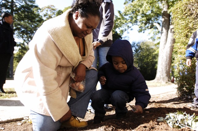 Stephanie Ware, program assistant at the CDC, and Damien Noeil, 4, cover a bulb with soil. The bulbs  planted during  will blossom in time for Alcohol Awareness Month. Ware, of Atlanta, said the planting would also help Noeil, son of Damien and Tonya Noeil, an administrative clerk at the CDC, and his classmates learn about the seasons.