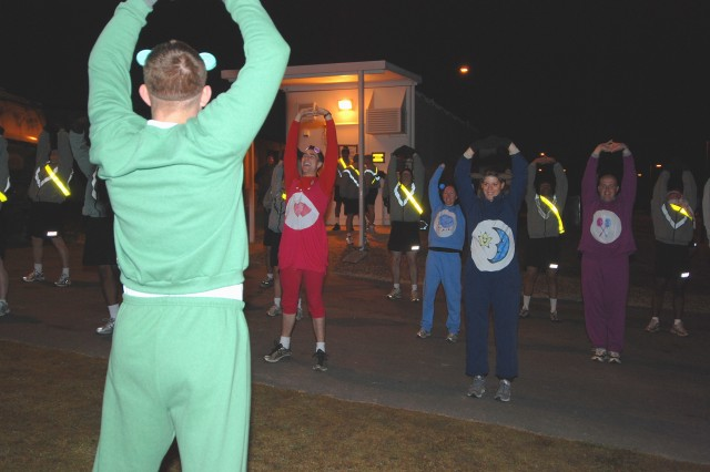 The Green Carebear, Sgt. Garrett Anderson, stretches out Headquarters Company, 2nd Brigade Combat Team, 82nd Airborne Division, for the Halloween run. HHC was given the opportunity to dress up for Halloween Friday morning. (U.S. Army photo by Sgt. Susan Wilt, 2nd BCT, 82nd Abn. Div. PAO)