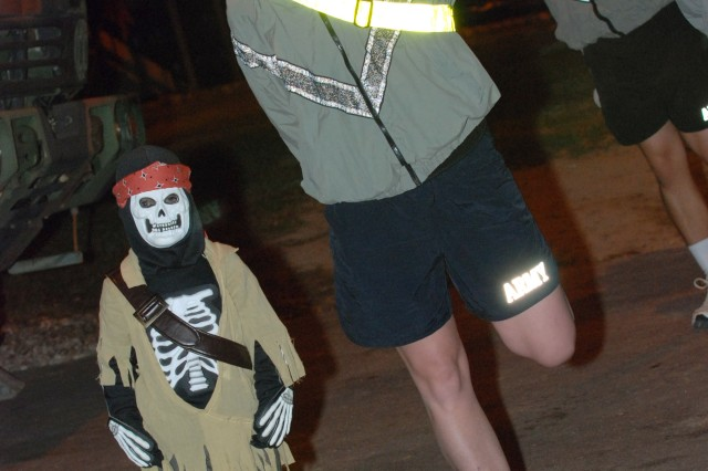 Sgt. Jennifer Thompson a member of Headquarters Company, 2nd Brigade Combat Team, 82nd Airborne Division, stretched out for the morning run while her son, the scary pirate, gets ready to spook those that see him. To celebrate the holidays family member of the Paratroopers from HHC came in for a Halloween fun run.  (U.S. Army photo by Sgt. Susan Wilt, 2nd BCT, 82nd Abn. Div. PAO)