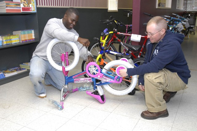 First Sergeant Lonnie Corley (left) and Staff Sgt. Matthew Wyatt, both of 17th Fires Brigade, assemble a bicycle Oct. 25 at Santa's Castle, for Make a Difference Day.
