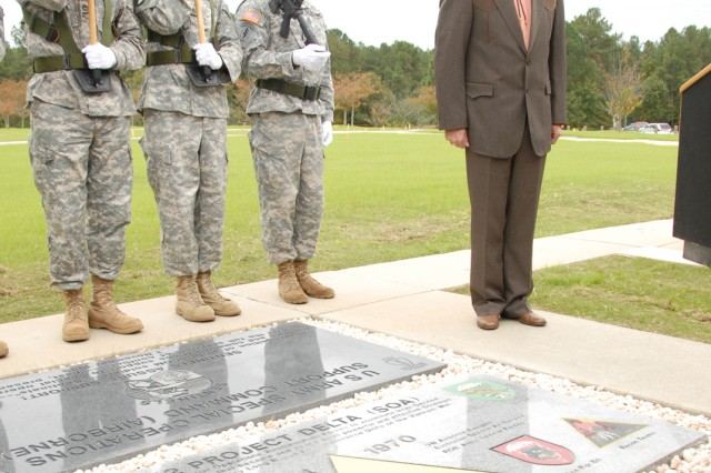 """Retired Command Sgt. Maj. Alton """"Moose"""" Monroe, a recon team leader and NCOIC, stands by the project's memorial stone during a dedication ceremony at USASOC headquarters Oct. 24. (Photo by Spc. Tony Hawkins, USASOC PAO)"""