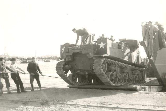 1st Armored Division M7 Being Unloaded at Algerian DocksThe lack of specialized tank landing craft during the Operation TORCH landings necessitated the capture and use of ports and docks to unload heavy vehicles, such as this Howitzer Motor Carrier M7 being unloaded at the Algerian docks on November 9, 1942. In future amphibious assaults Landing Ship Tank vessels, or LSTs, enabled tanks and other armored and unarmored vehicles to be unloaded directly onto invasion beaches ready for combat. (World War II Signal Corps Photograph Collection).
