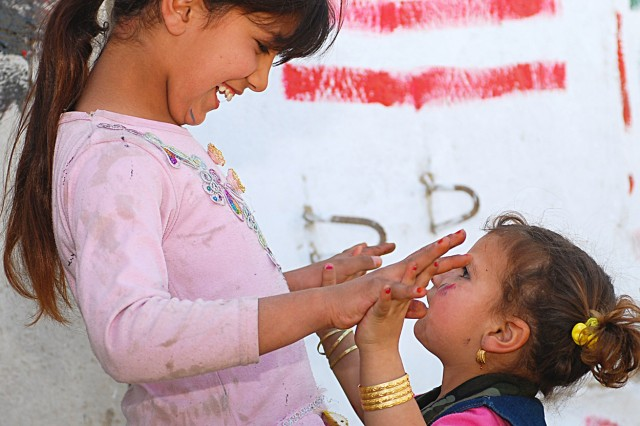 Two Iraqi girls celebrate after adding their creations to the wall. The structure borders a path leading from the children's village to their school.