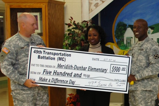 Lt. Col. Pete Haas, the commander of the 49th Transportation Battalion, 15th Sustainment Brigade, 13th Sustainment Command (Expeditionary), and Command Sgt. Maj. Ricky Knox, the battalion's senior noncommissioned officer, present a $500 check to Wanda Reynolds, the principal of Meredith Dunbar Elementary School, Oct. 27 at the school in Temple. The money was raised by the battalion as a part of Make A Difference Day, the national day of helping others, and presented to school to help fund field trips.