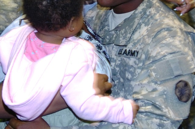 Spc. Joshua Gillard, a truck driver with the 418th Transportation Company, 180th Transportation Battalion, 15th Sustainment Brigade, hugs his wife C'alace and daughter Jordan Nov. 3 at the Kieschnick Physical Fitness Center on Fort Hood. About 200 Soldiers from the 13th Sustainment Command (Expeditionary) returned home during the ceremony.