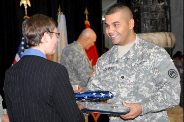 Spc. Jose Aguirre-Delgado receives an American flag from Lori Pietropaoli, deputy director, U.S. Citizenship and Immigration Services, Nov. 4, 2008, during a U.S. citizenship ceremony at Al Faw Palace on Camp Victory, Iraq.