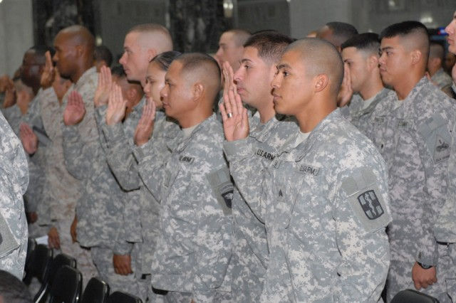 Servicemembers from across Iraq raise their right hands together Nov. 4, 2008, taking the oath of U.S. citizenship during a naturalization ceremony at Al Faw Palace on Camp Victory, Iraq.