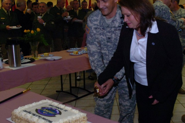 Hohenfels, Germany -- Col. Charles A. Preysler (left) joins with his wife, Lisa, in cutting the ceremonial cake after taking command of the Joint Multinational Readiness Center. Preysler took command of the Joint Multinational Readiness Center during an Oct. 21 ceremony at the post gymnasium.