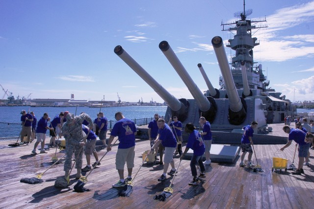 Alpha Company, 205th Military Intelligence Battalion Soldiers swab the deck of the USS Missouri, Oct. 24 as part of their unit's volunteer day. The Company was broke up in to three groups: deck swabbers, painters and shoreline cleaners.