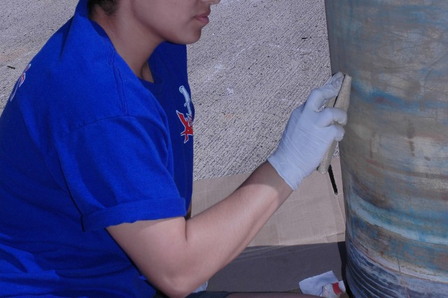 Pvt. Jenny Carlo of Alpha Company, 205th Military Intelligence Battalion, 500th MI Brigade sands an old shell before painting it.  Carlo's company used cleaning up the Missouri as the unit's volunteer day activity Oct. 24.