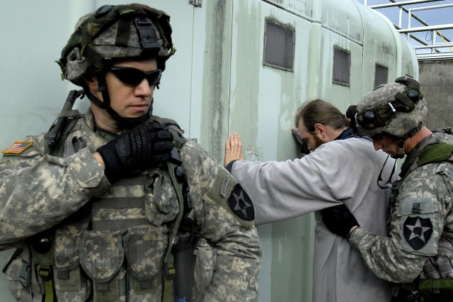 """Soldiers from 1-23 Inf.  search a civilian for weapons Monday during """"Operation Tomahawk Shock,"""" a platoon-level situational training exercise as part of the 3rd Bde., 2nd Inf. Div.'s preparation for deployment to Iraq next year."""