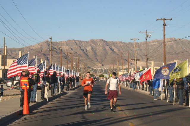Capt. Kevin Lockett of 2nd Battalion, 6th Air Defense Artillery Brigade, left, and Pvt. Matthew Zumbrun of 6th Squadron, 1st Cavalry Regiment, reach the finish line of the five-kilometer portion of the Wounded Warrior Walk/Run Saturday, running past flags held by members of the Patriot Guard Riders.
