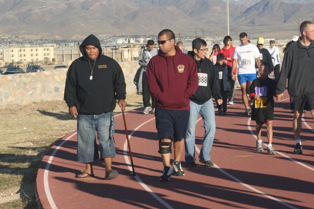 Sgt. Ronald Gan, left, and Cpl. Reynaldo Rivera, both Soldiers with Fort Bliss' Warrior Transition Battalion, walk the track at Stout Physical Fitness Center during the one-mile walk event at the Wounded Warrior Walk/Run Saturday morning.