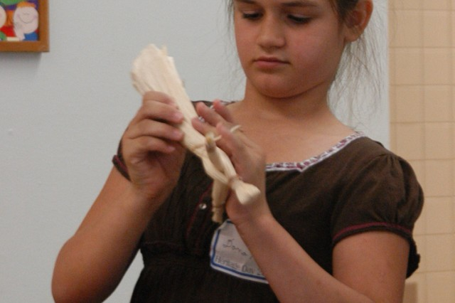 Dana Nolen, 10, participates in Heritage Days activities for children by making a corn husk doll.