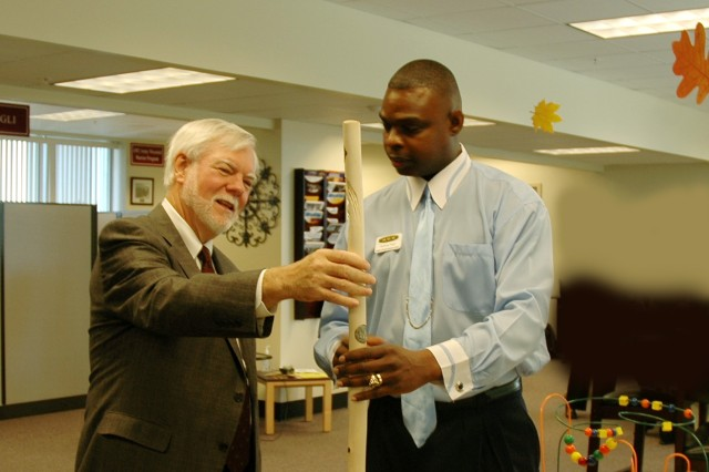 Honorable Nelson M. Ford, Under Secretary of the Army, admires one of the walking sticks carved by a Wounded Warrior with Anthony Pugh, Outreach Coordinator for the Fort Bragg Solder & Family Assistance Center.