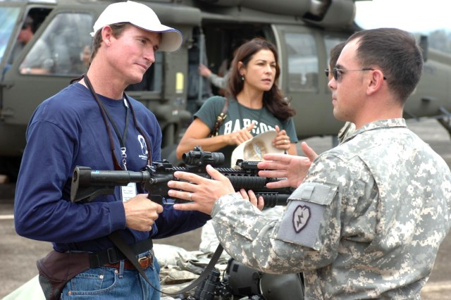 Dr. Charles R. Kelley, MD, Vice President, KF Development, holds an M4 Carbine while listening to Warrant Officer 2 Michael Parreco, helicopter aviator, 2nd Battalion, 25th Aviation Regiment, 25th Combat Aviation Brigade, describe other UH-60, Blackhawk, weapon systems during the Young Presidents Organization's visit to Wheeler Army Airfield, Nov. 5. (Photo by: Sgt. Mike Alberts, 25th Combat Aviation Brigade Public Affairs)