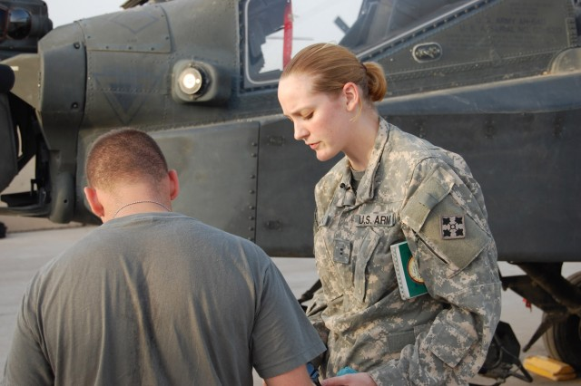 Chief Warrant Officer 2 Nicole Shuman, Apache attack helicopter pilot, Headquarters and Headquarters Company, Combat Aviation Brigade, 4th Infantry Division, Multi-National Division-Baghdad, who hails from Pittsburgh, talks with a fellow crew member before taking off on a reconnaissance patrol from Camp Taji Oct. 27.